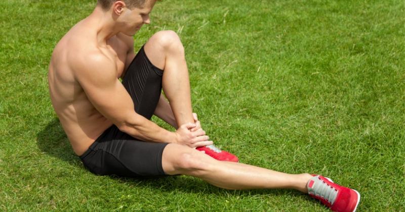 En man som sitter i gräset och tar sig på benet.